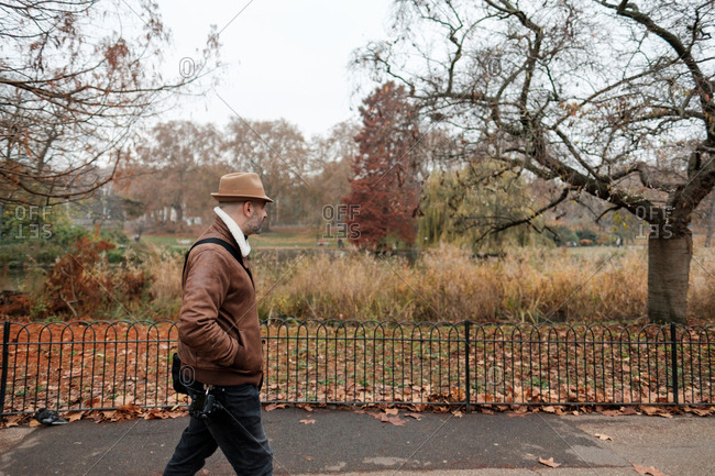 Side view of adult man in casual outfit holding hands in pockets walking near fence in tranquil autumn park in London