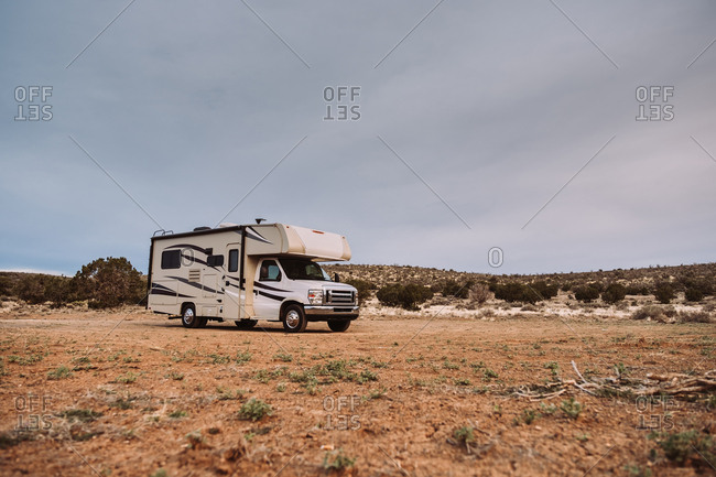 Contemporary travelling camper parked on deserted valley by hills in USA