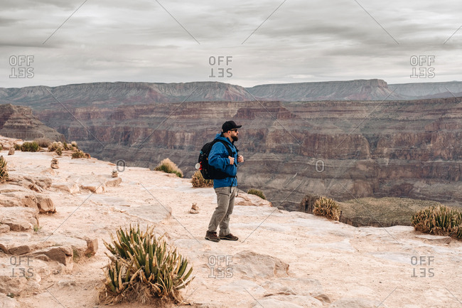 Side view of man with backpack admiring picturesque view of canyon in USA
