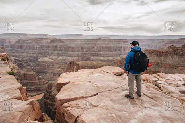 Back view of man with backpack admiring picturesque view of canyon in USA