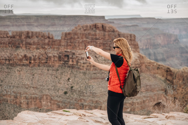 Side view of woman with backpack shooting picturesque view of canyon in USA