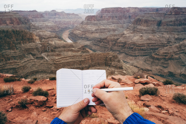 Crop man making notes in diary while having rest at edge of cliff in canyon in USA