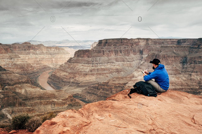 Side view of tired man relaxing on edge of cliff at canyon in USA and drinking coffee