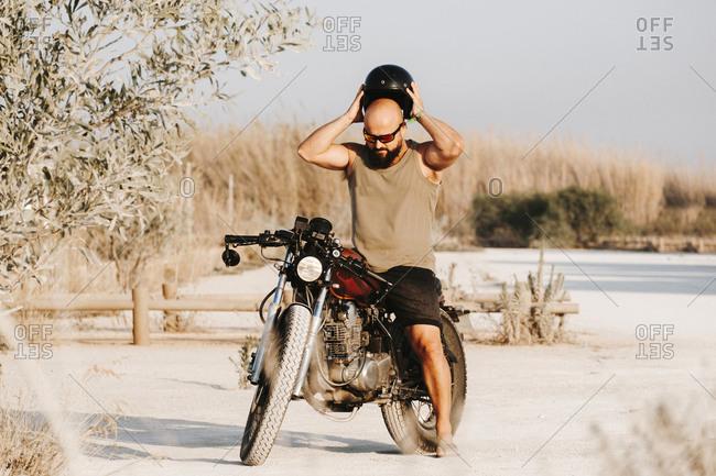 Brutal bald man in helmet and sunglasses having break on motorcycle on field