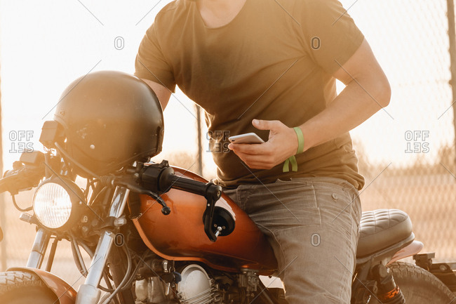 Man sitting on motorcycle and surfing mobile