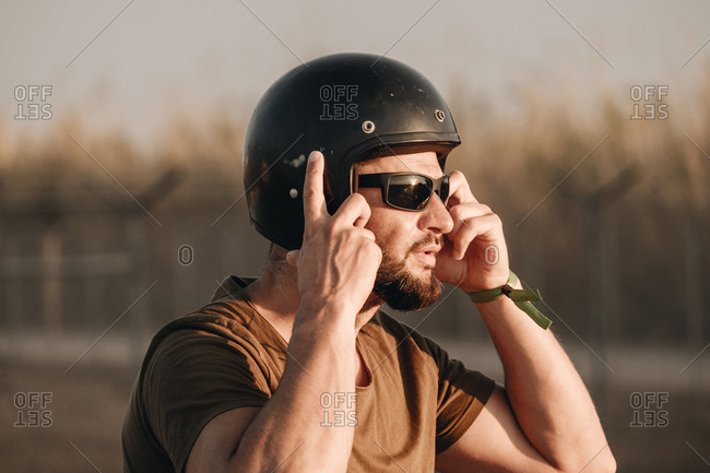 Side view of brutal bearded man in sunglasses and helmet on blurred background