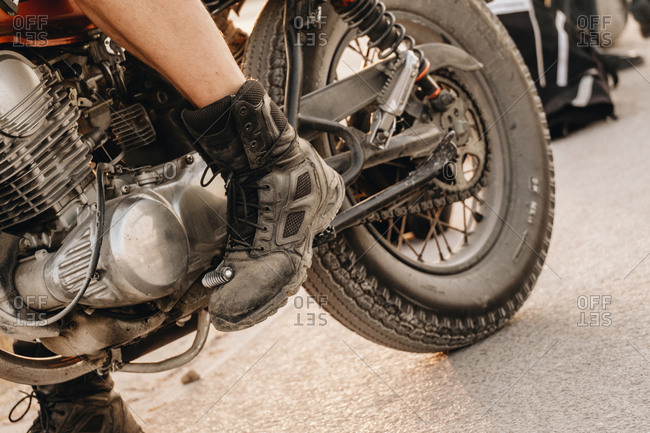 Crop brutal man in worn boots pressing gearbox pedal on motorcycle