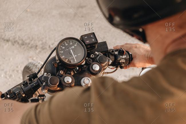 Crop man in helmet riding motorcycle and looking at speedometer