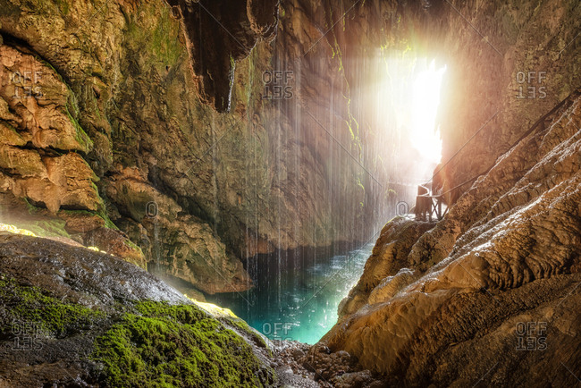 Scenic tropical cave with underground river and pathway with railing in sunlight