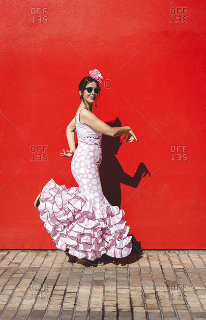 Side view of eccentric cheerful woman in colorful pink costume smiling and dancing by red wall background on sunny day