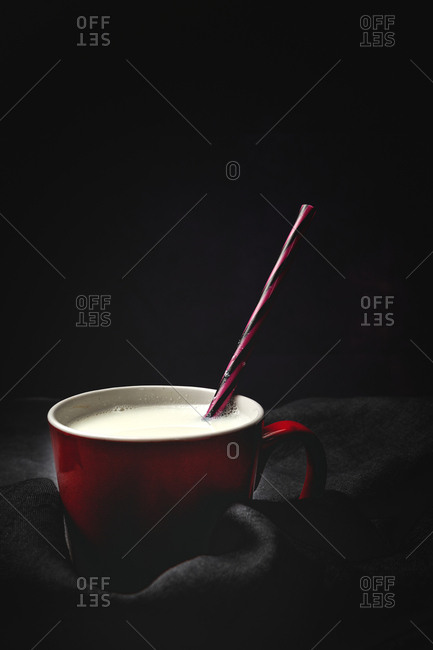 Cup of white milk with bright striped straw on table over black background