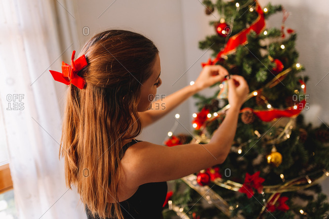 Happy young woman decorating Christmas tree with ball at home