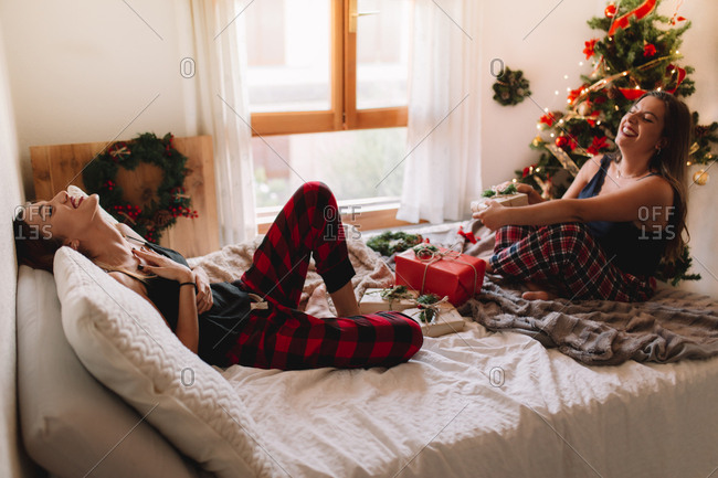 Two beautiful friends laughing in bed at home near Christmas tree in cozy interior. Interior with Christmas decorations.