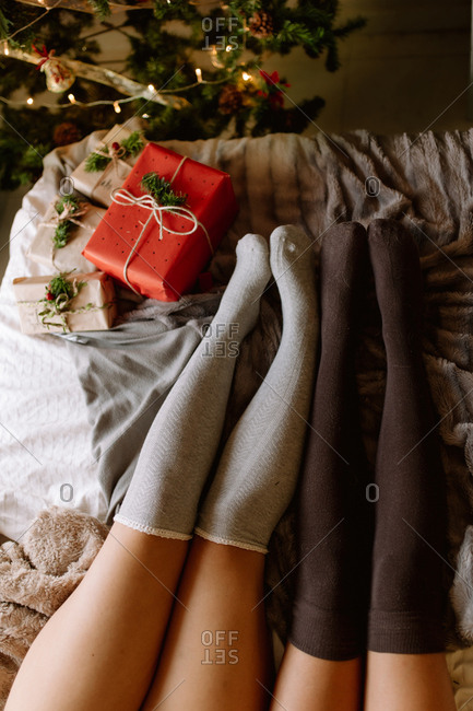 Two friends with knee high socks in winter holidays at home near Christmas tree in cozy interior with Christmas presents.