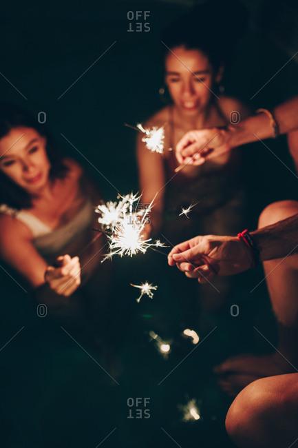 Cheerful friends burning sparkles near pool