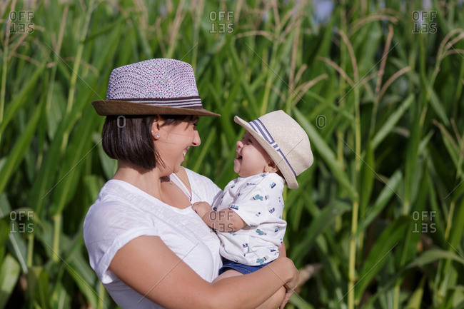 Side view of stylish joyful mother and kid on hand having time together smiling in sunny day in green agricultural field