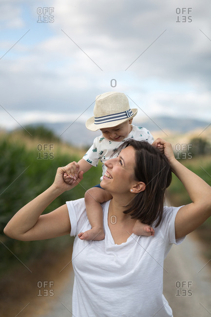 Adorable kid in hat on shoulders and looking at mother