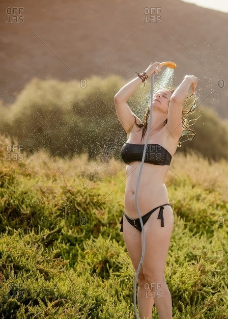 Relaxed woman touching hairs and taking shower putting face under water in swimsuit in green field in light day