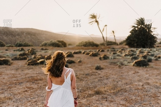Woman in white dress in dry field in sunlight