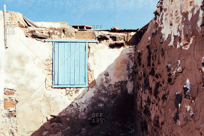 Window shuttered by blue wooden shutters in clay old wall of shabby ancient building in Fuerteventura, Las Palmas, Spain