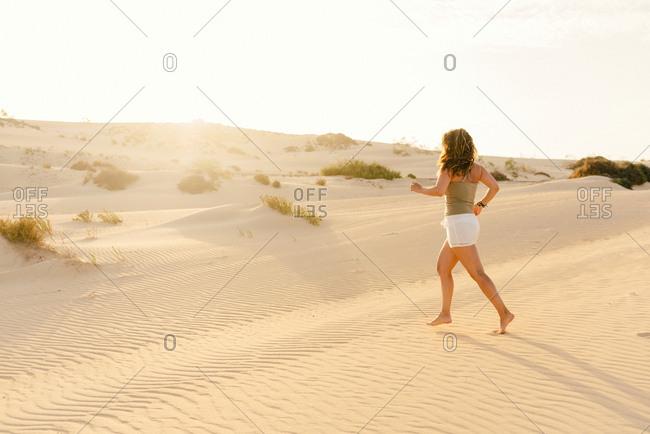 Side view of sporty energetic woman in comfortable clothing running in hot dry desert in Fuerteventura, Las Palmas, Spain