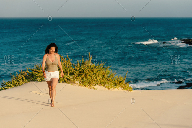 Tanned slim woman in white shorts barefoot on sandy shore with plant on background of turquoise foamy waves in Fuerteventura, Las Palmas, Spain