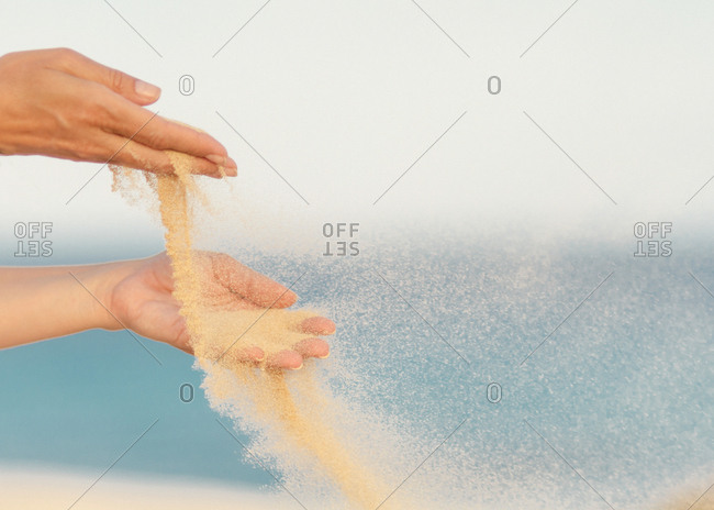 Woman releasing sand in hands in wind