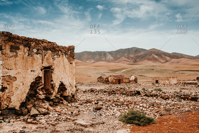 Breathtaking landscape of old abandoned brick houses in dry desert surrounded by mountains in Fuerteventura, Las Palmas, Spain