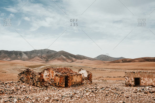 Dilapidated old buildings in mountain desert under cloudy sky
