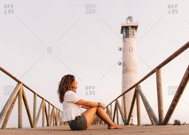 Woman sitting on bridge to lighthouse and looking away