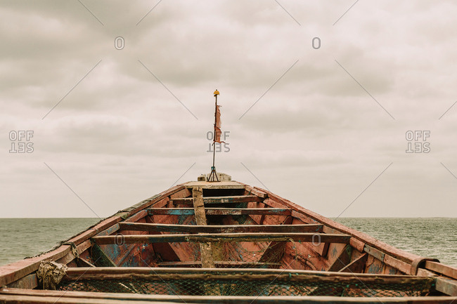 Aged shabby vessel with flag floating on rippling sea water against cloudy sky in Gambia