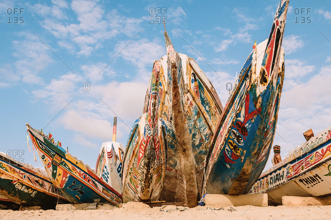 Gambia - August 3, 2019: Colorful bright boats placed on sandy shore with bows to blue sky
