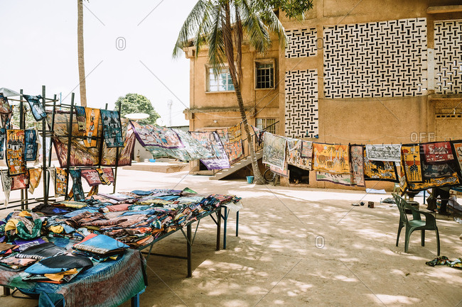 Gambia - August 6, 2019: Bright colorful shawls with creative design scarves made of fabric beads on tables and ropes for sell on street market in ancient yard