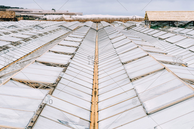 From above warehouse and transparent closed and opened polycarbonate roofs of hothouses on horticulture farm during daytime in overcast weather on blurred background