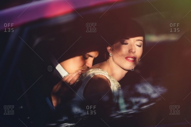 Side view of passionate groom kissing bride on back while woman closing eyes in pleasure in wedding trip in car