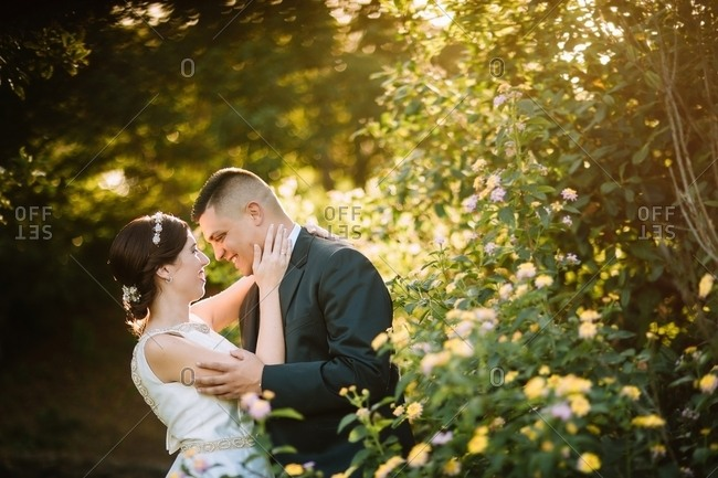 Side view of graceful tender wedding couple bonding and looking to eyes with love among bright yellow flowers and bushes in garden