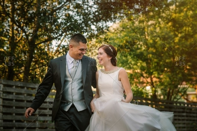 Happy just married couple running along fence in garden