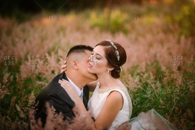 Smiling groom and bride hugging and kissing in park