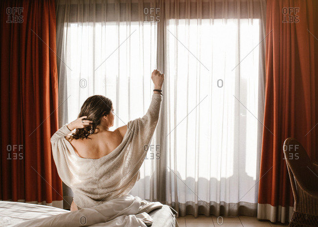 Back view of adult female with raised arm looking away and touching hair while sitting on bed against closed window with red curtains and white tulle in sunny morning