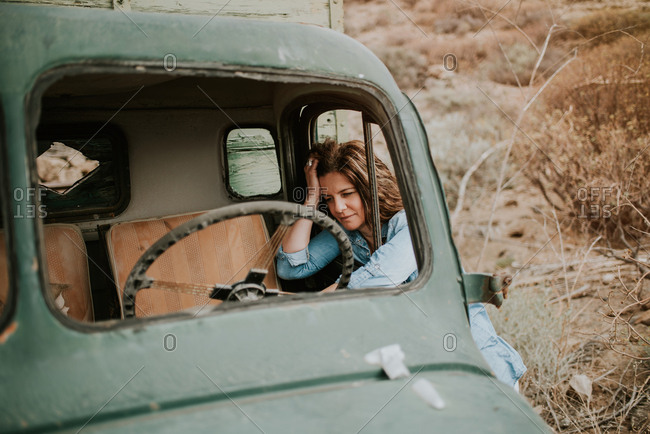 Thoughtful young woman in shorts and denim shirt standing leaning in a windows of a green truck with wooden body and looking away on nature background