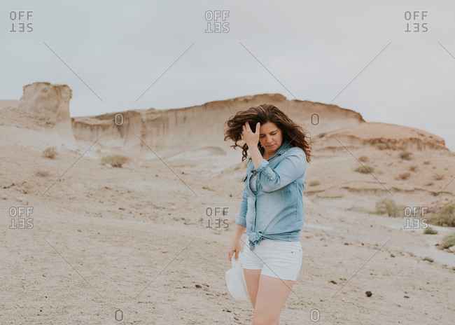 Positive woman in casual clothes walking holding a hat by sandy dunes and looking down on gloomy day
