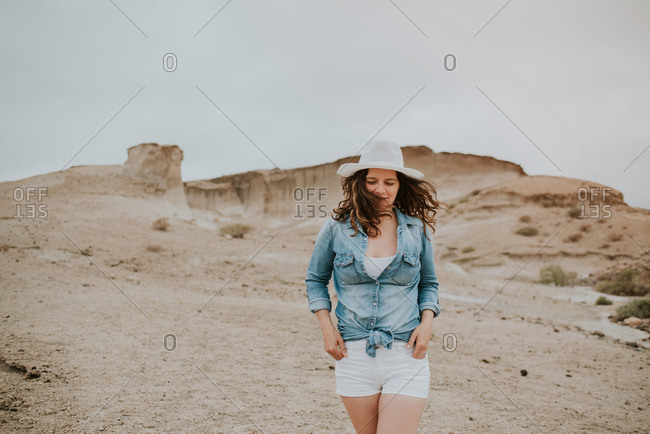 Positive woman in casual clothes wearing a hat walking with hands in pockets by sandy dunes and looking away on gloomy day
