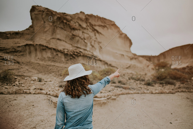 Back view of unrecognizable woman in casual clothes standing on desert sandy dunes and pointing out on gloomy day