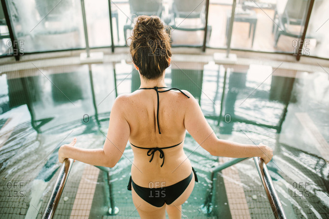 Back view of young woman in black bikini going into water in wellness center on daytime