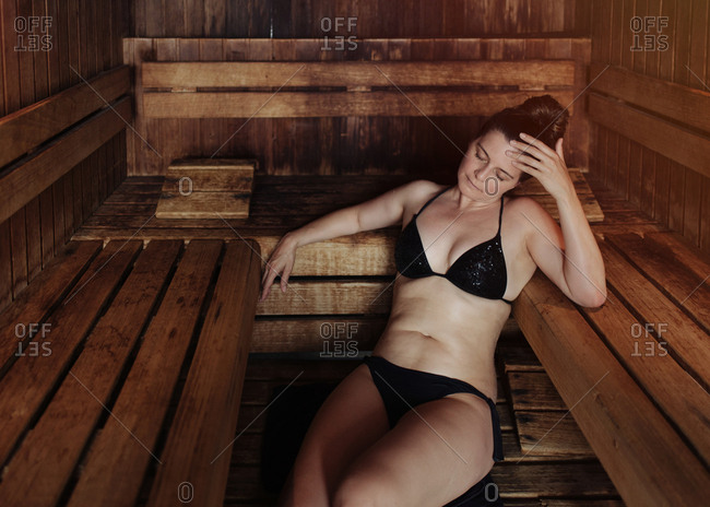 Woman in black bikini sitting with closed eyes on towel in steam room leaning on wooden bench and enjoying heat