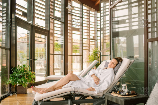 Side view of adult woman in white bathrobe lying with closed eyes on daybed after spa procedures in modern salon