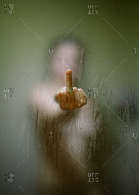 Through wet glass view of faceless woman showing middle finger while taking shower