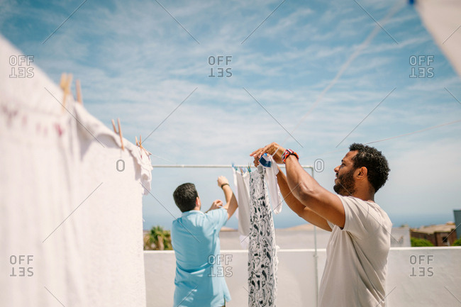 Multiracial men hanging clothes in bright day