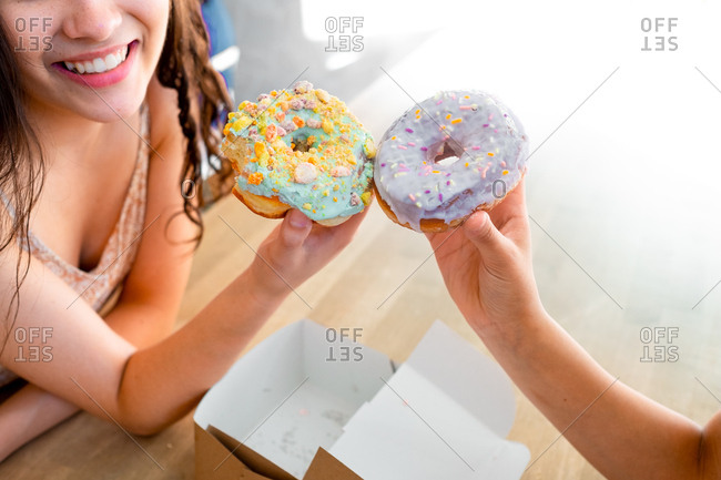 Crop from above women in sundress carrying round glazed pastry with sprinkles while sitting by table on sunny day
