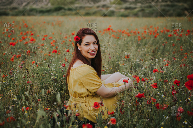 Pensive attractive red haired adult lady in yellow dress with red poppy in hair and red lips looking over shoulder